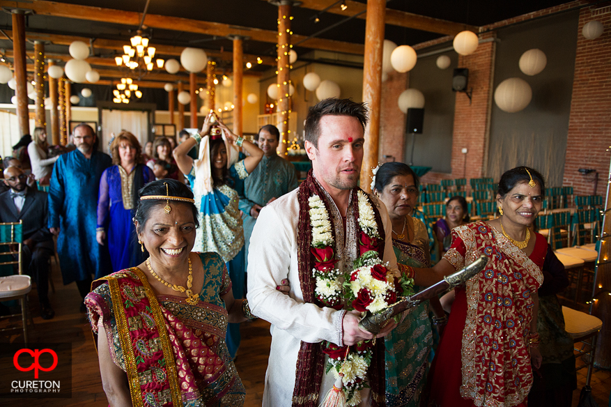 Bride's mother leads the groom to the mandap