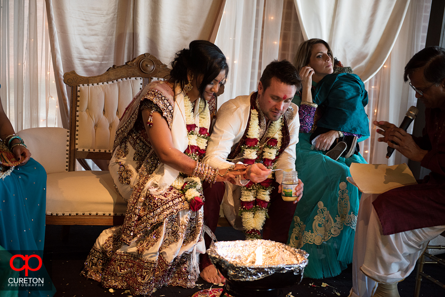 Bride and groom put items in the fire their Indian wedding in Greenville,SC..