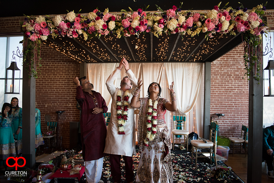 Bride and groom throw rice into the air during their Indian wedding in Greenville,SC..