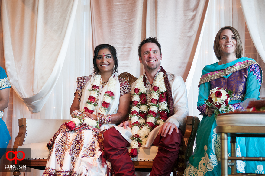 Bride and groom sitting under the mandap.