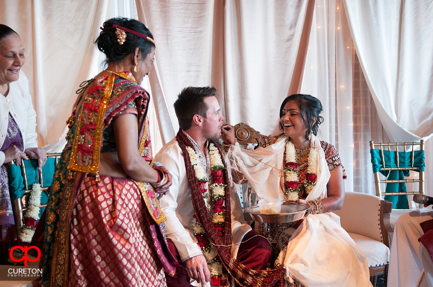 Bride feeds groom during the traditional Indian ceremony.