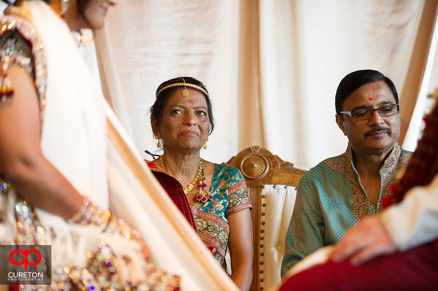 Bride's mother gazes at her daughter during the Indian wedding.