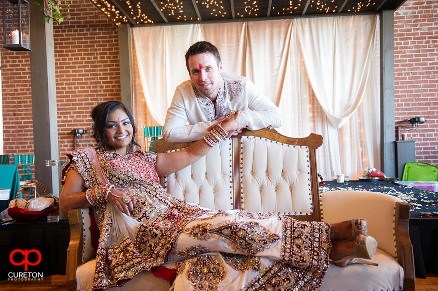 Bride and groom pose under the mandap after their Indian wedding in Greenville,SC..