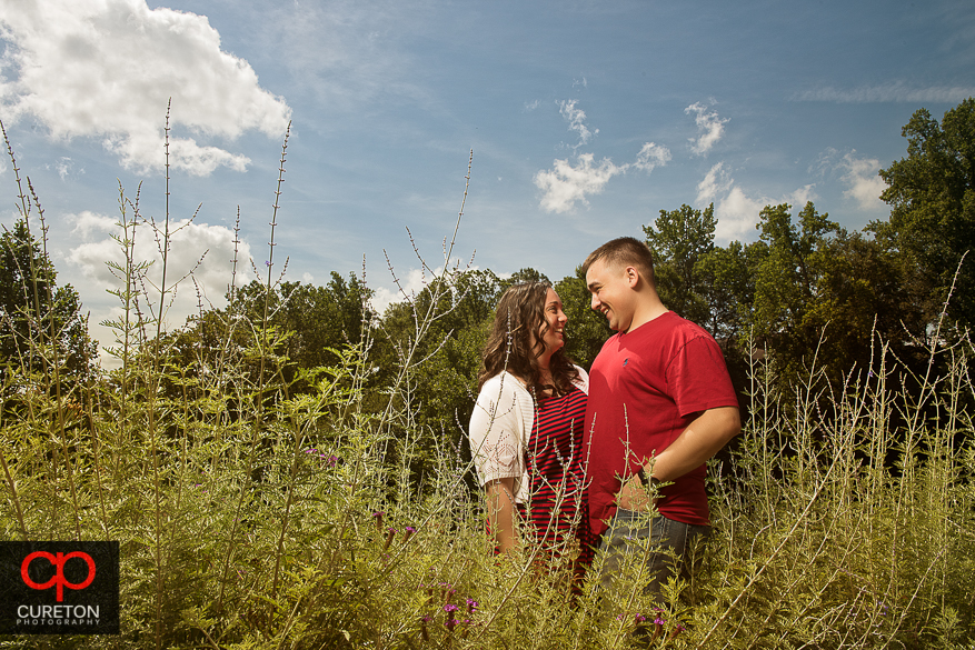 Couple standing in tall grass at Falls Park in downtown Greenville.