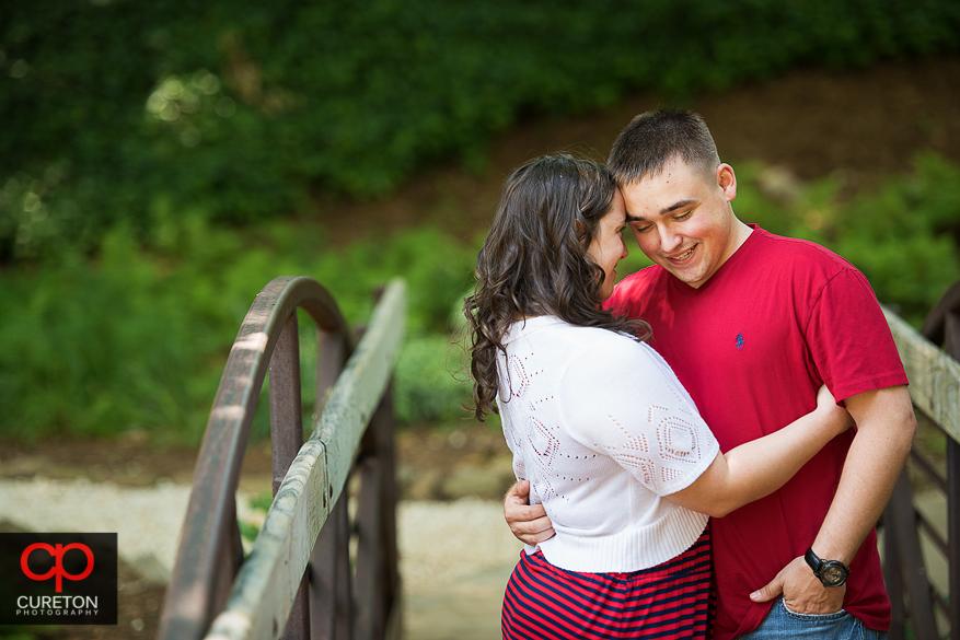 Couple hugging on the bridge in Greenville, SC.