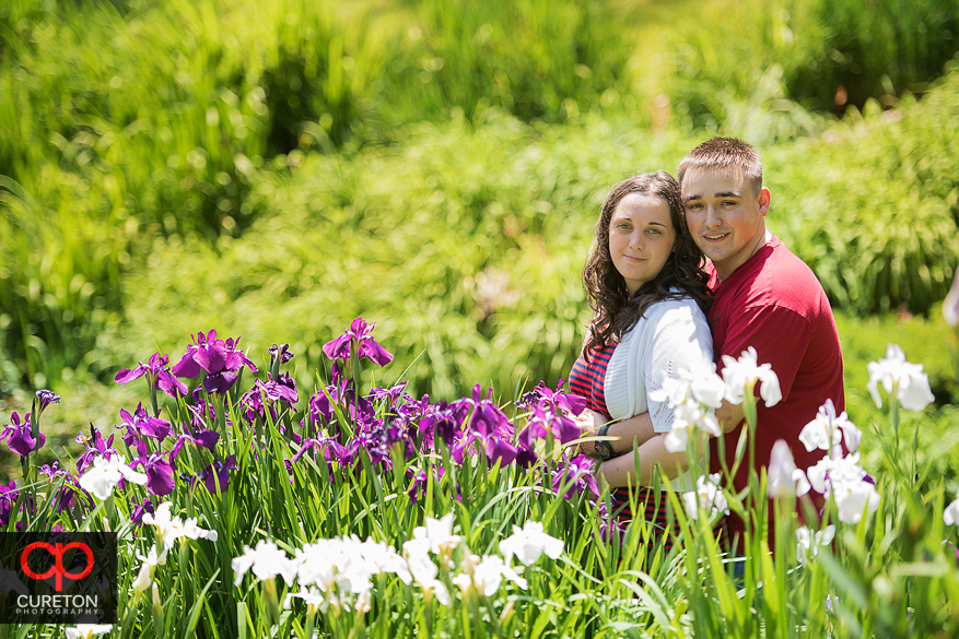 Engaged couple sitting in the flowers in downtown Greenville, SC.