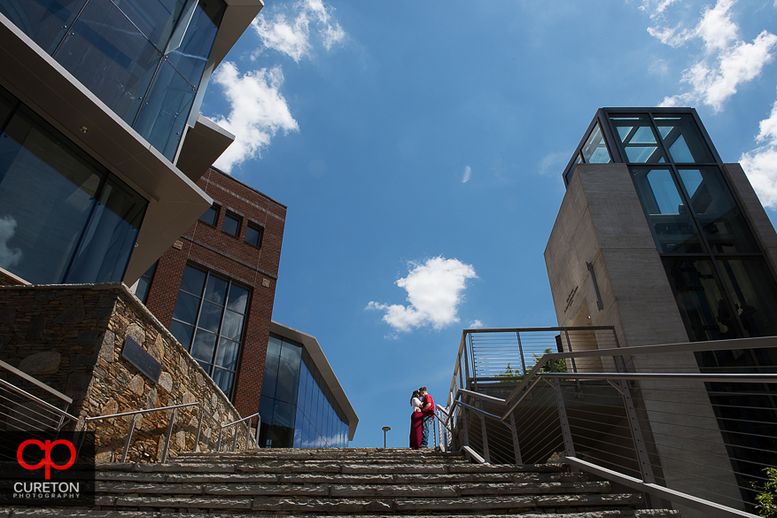 Photo of an engaged couple standing at the top of the steps behind the Peace Center in downtown Greenville.