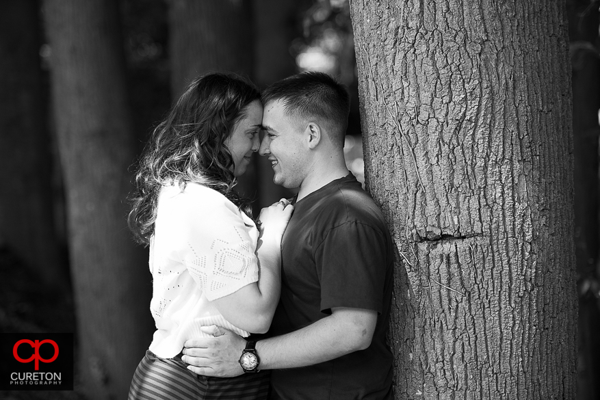 Romantic black-and-white photo of a couple leaning up against a tree in downtown Greenville, SC.