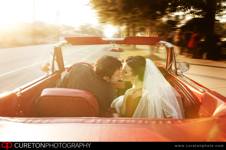 A couple leaving thier wedding in a vintage Mustang convertable.