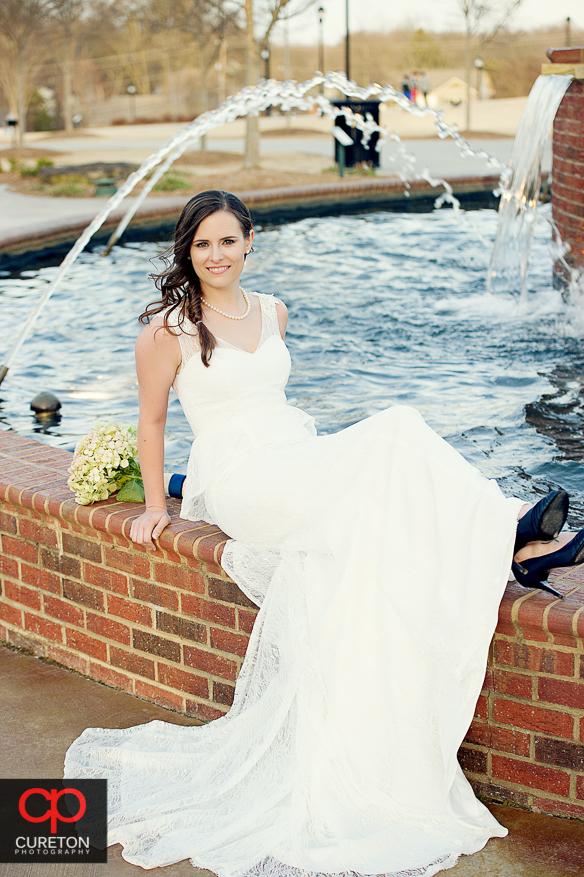 Bride sitting on fountain.