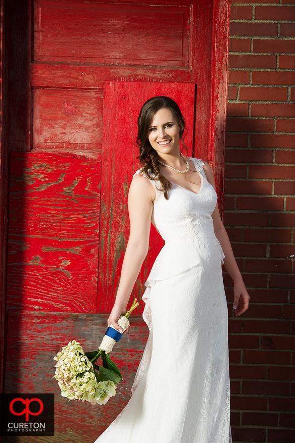 Smiling bride in front of red door.
