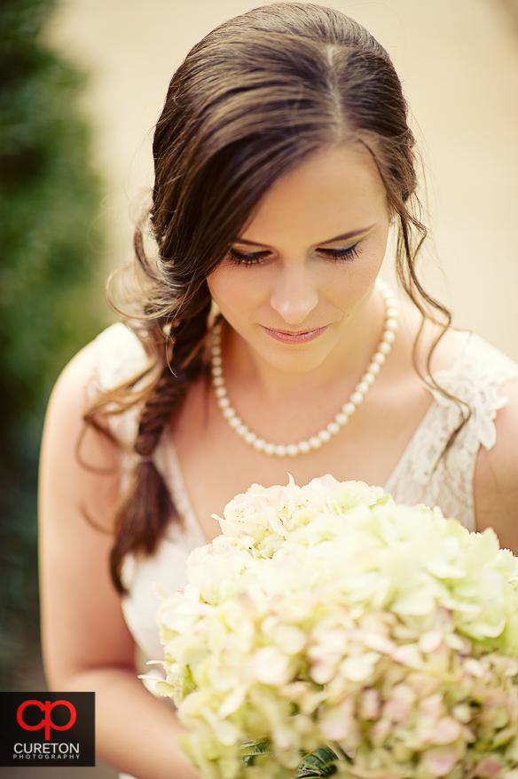 Bride looking at flowers.