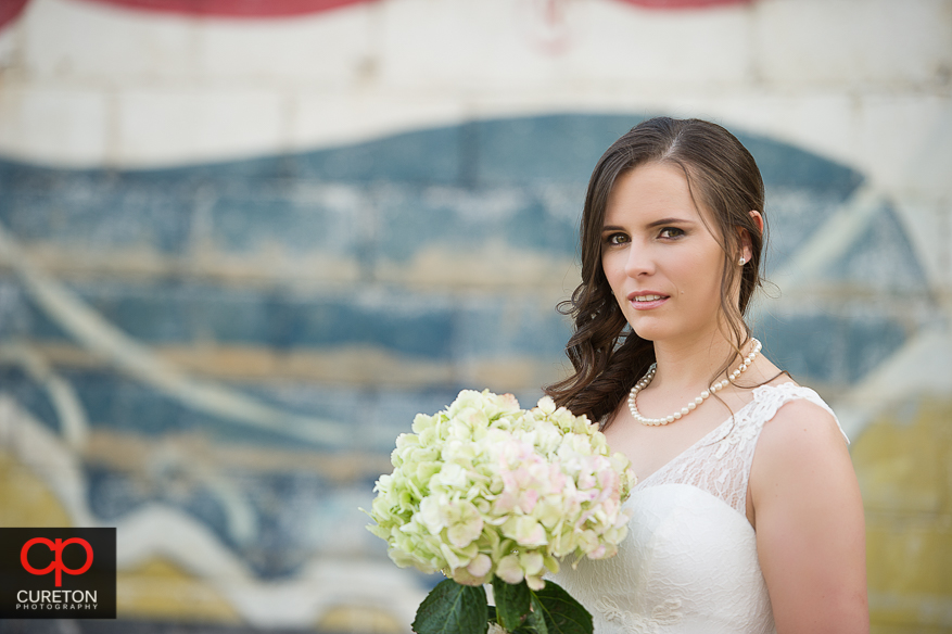 Bride in front of painted wall.