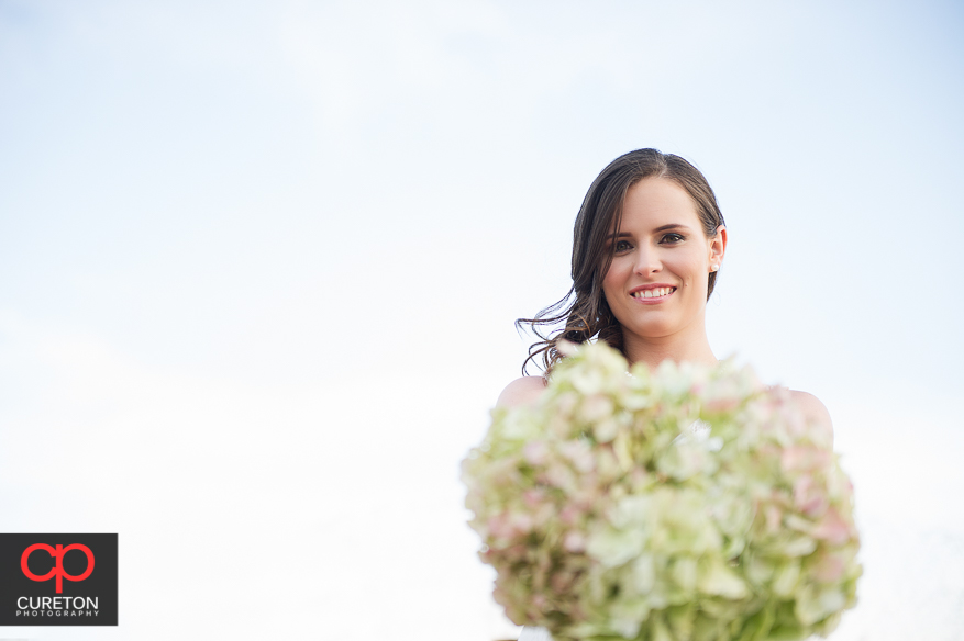 Bride with flowers and sky background.