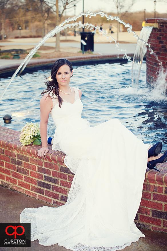 Bride sitting near fountain.