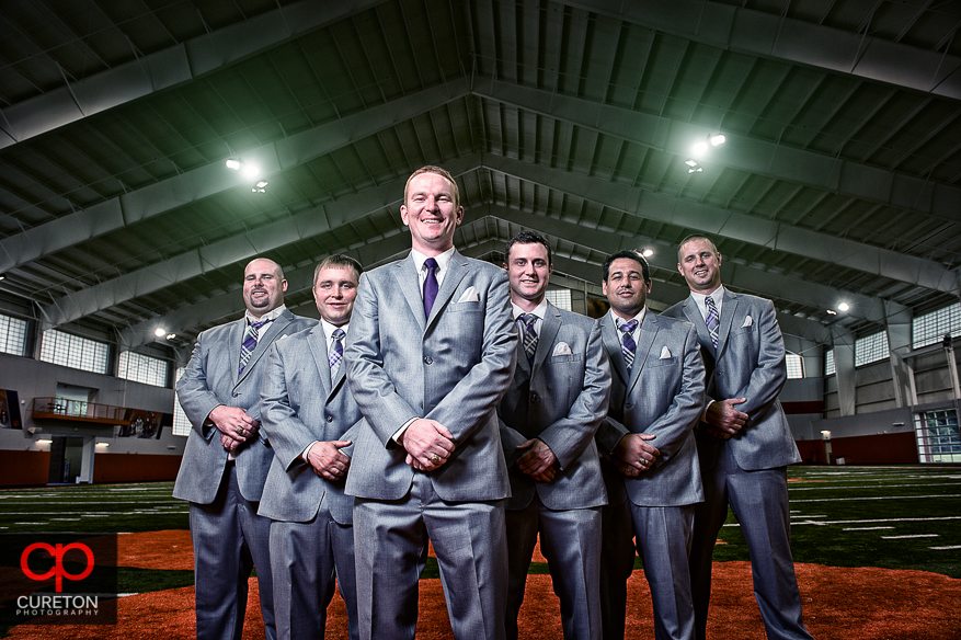 Groom and his groomsmen posing on the fifty yard line of the Clemson indoor football complex.