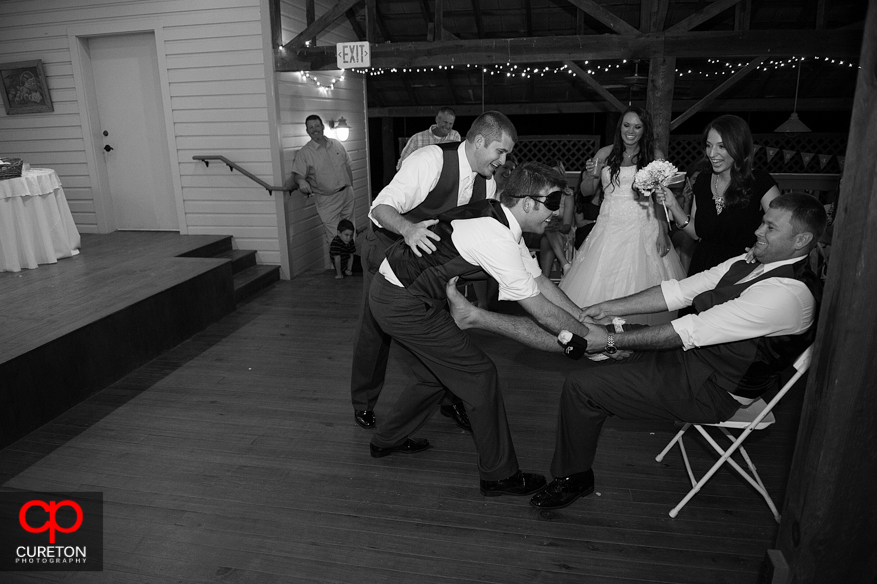 The groomsmen playing a trick on the guy that caught the garter.