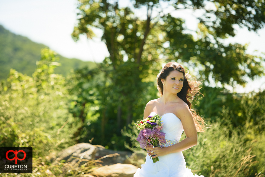 Bride standing in the direct sunlight in a mountain field.