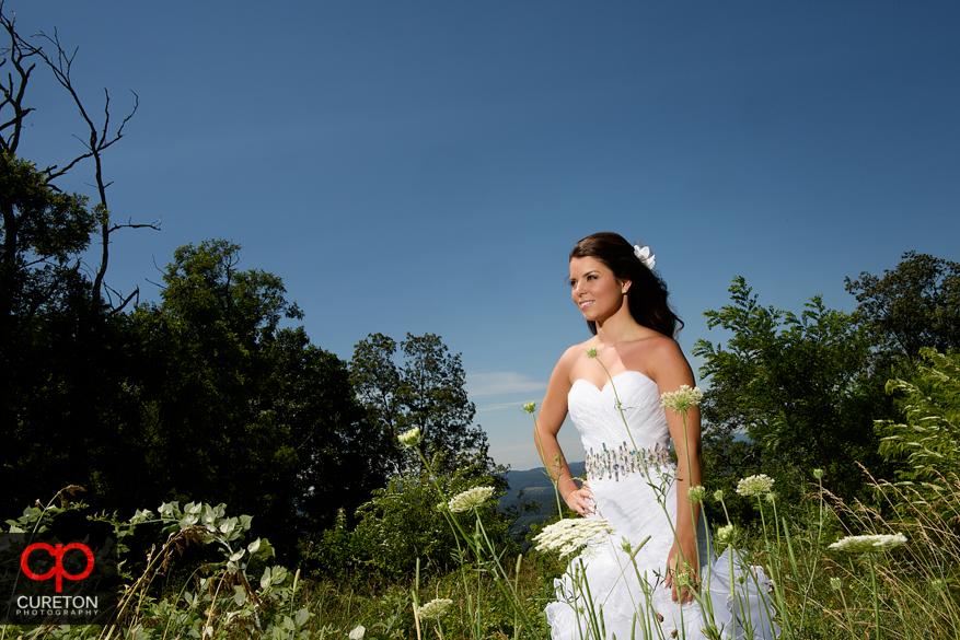Bride standin in a field of wild flowers.