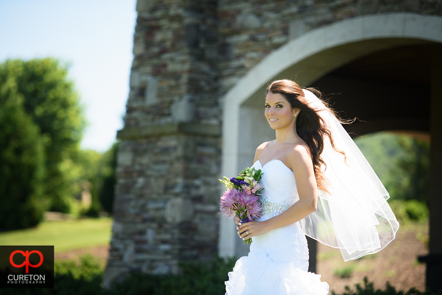 Bride in natural light with her veil blowing in the breeze.