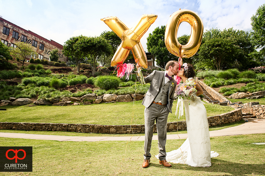 Couple on their wedding day holding X and O balloons in Falls Park in downtown Greenville,SC .