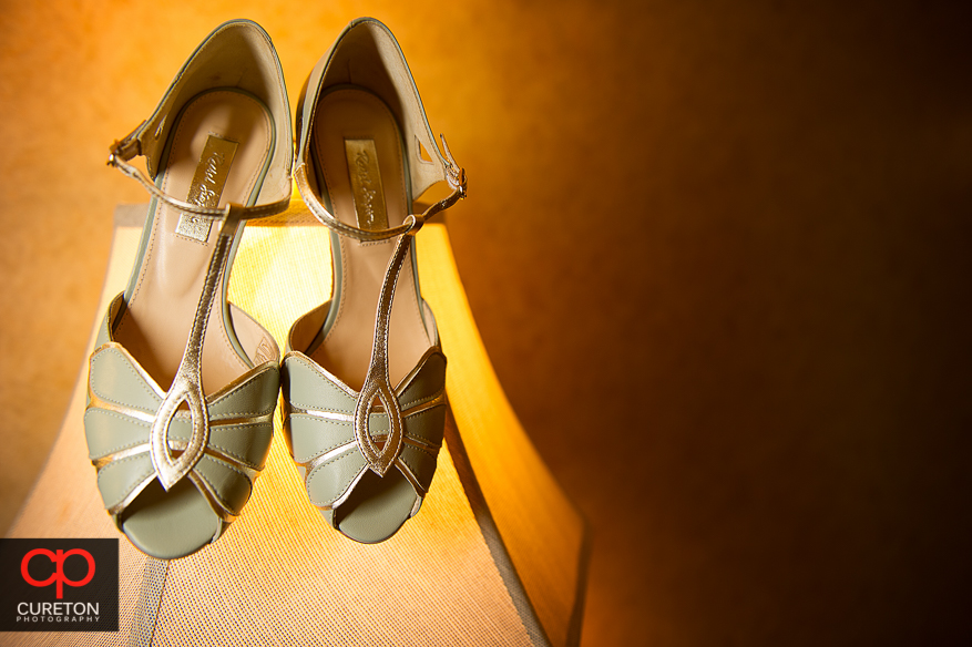 Bride's shoes hanging on a lamp before the wedding.