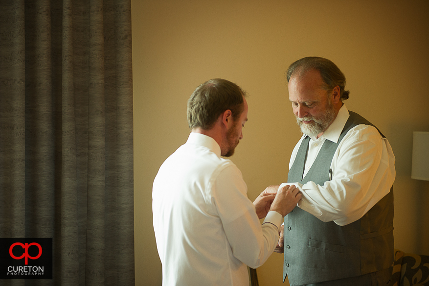 Groom helping his father get dressed.