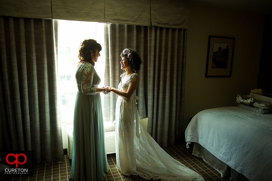Bride and her mother share a moment in the window.