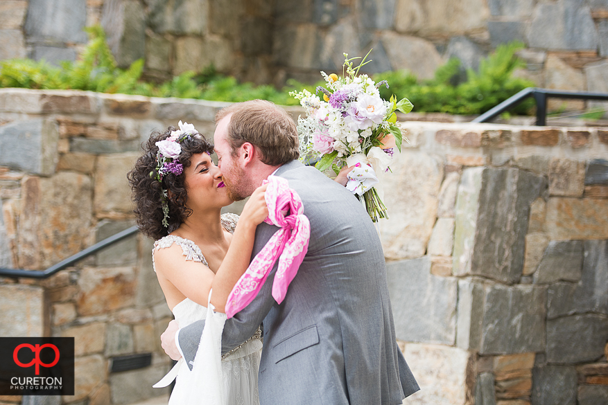 Bride and groom kiss during their first look in downtown Greenville.