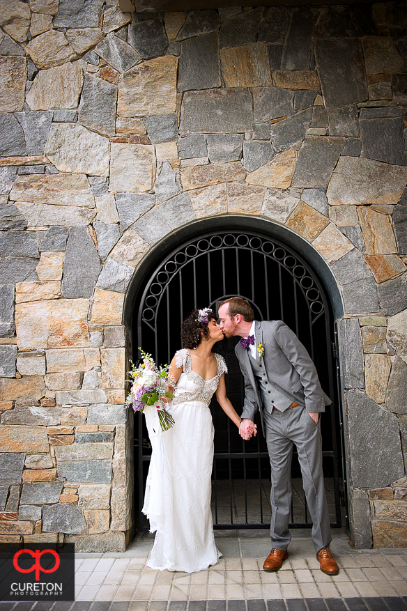 Bride and groom kissing in front of a gate.