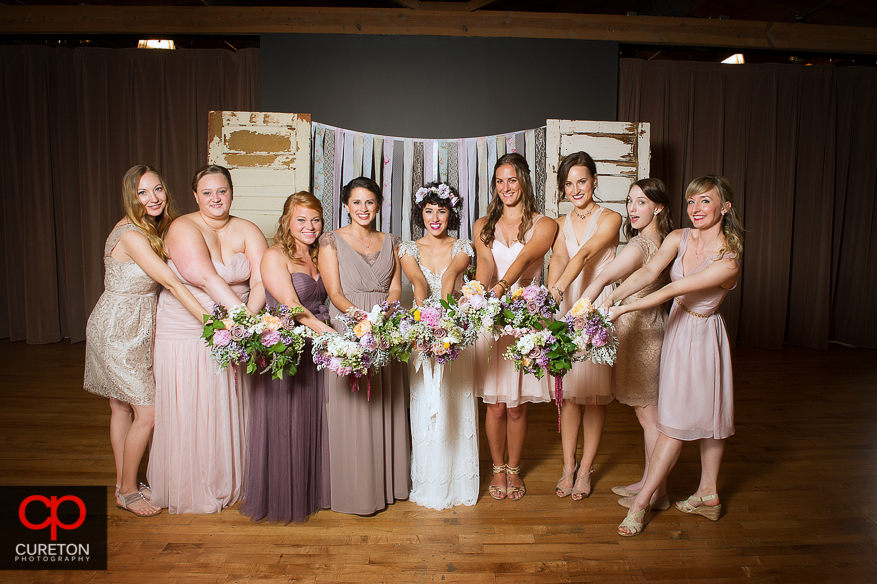 Bridesmaids holding flowers out.