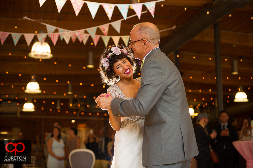 Bride smiles during her dance with her father.
