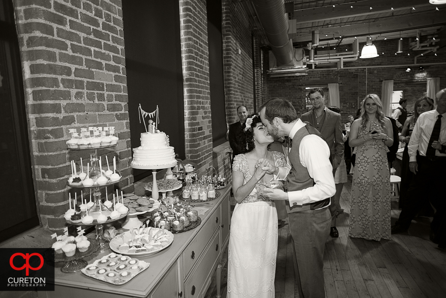 Coupe kissing at the cake cutting.