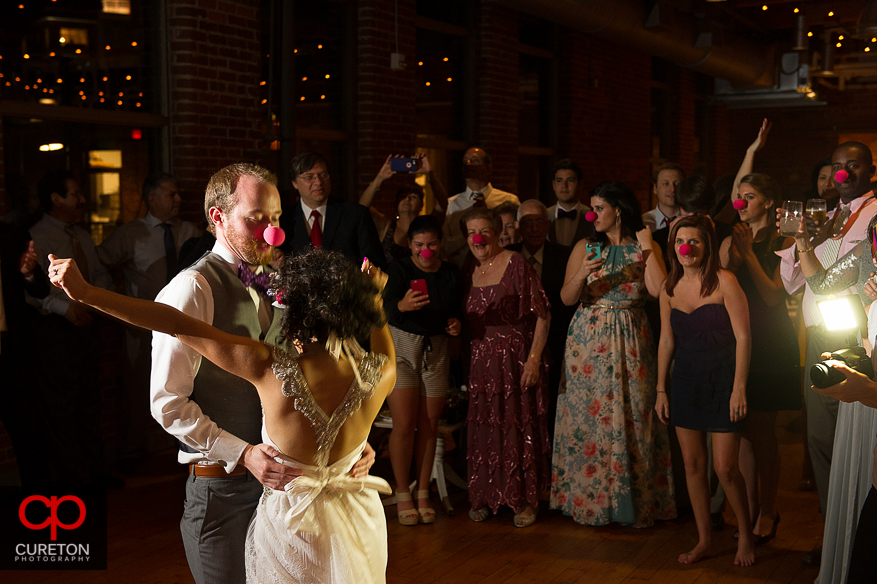 Bride and Groom dancing with red noses.