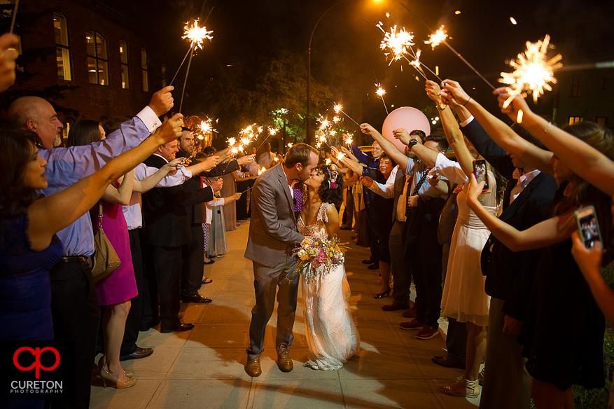 Bride and groom leave the Certus loft through sparklers.