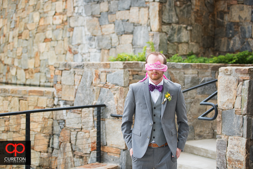Groom awaitin the first look while blindfolded .