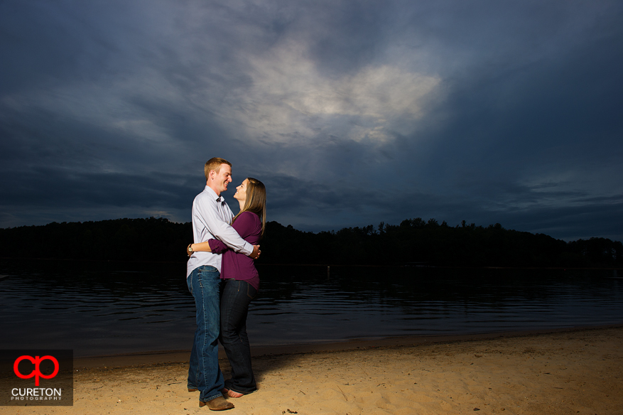 A couple standing on lake hart well beach at sunset.