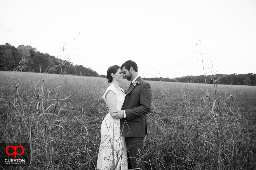 Bride and groom in tall grass.