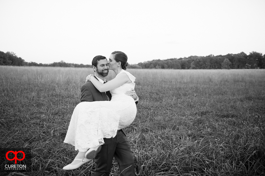 Black and white of groom carrying bride in a field.