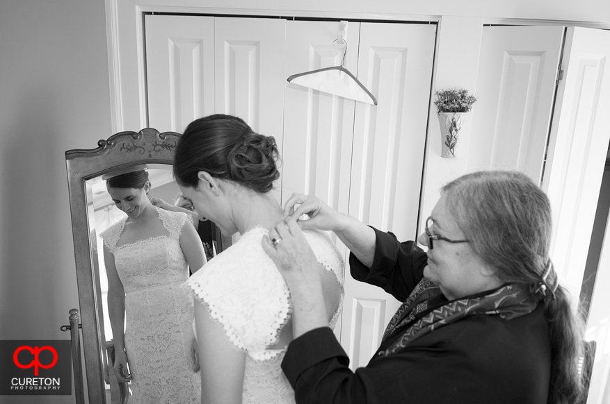 Mom helps bride into dress.