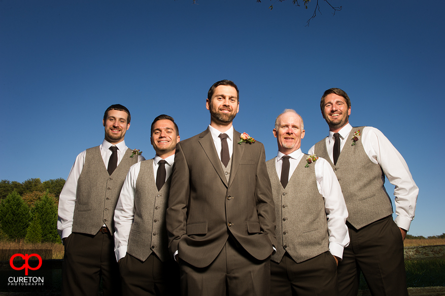 Groomsmen posing in the field at Lenora's Legacy.