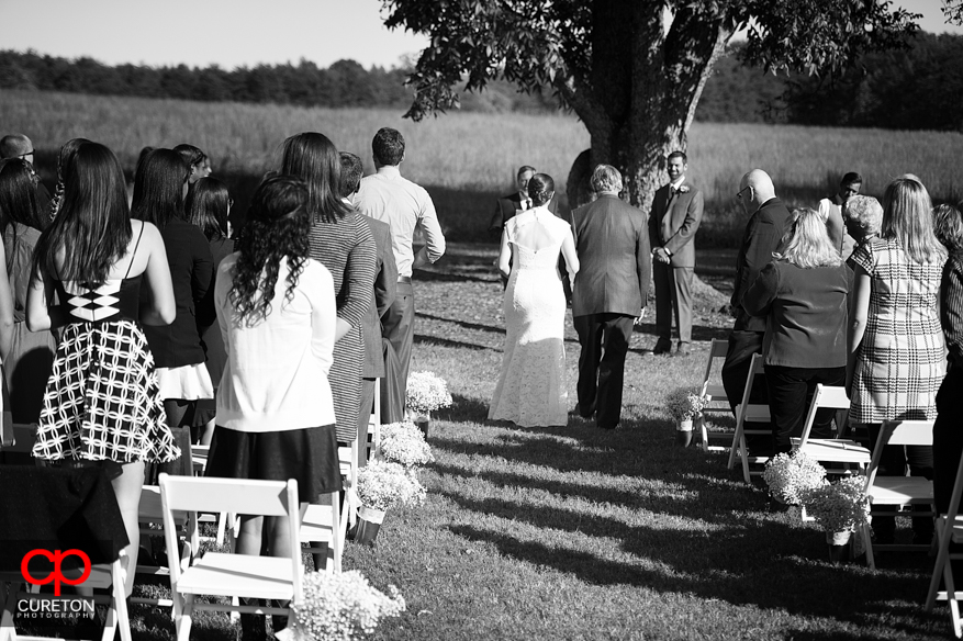 Black and white of bride and father walking down the aisle.