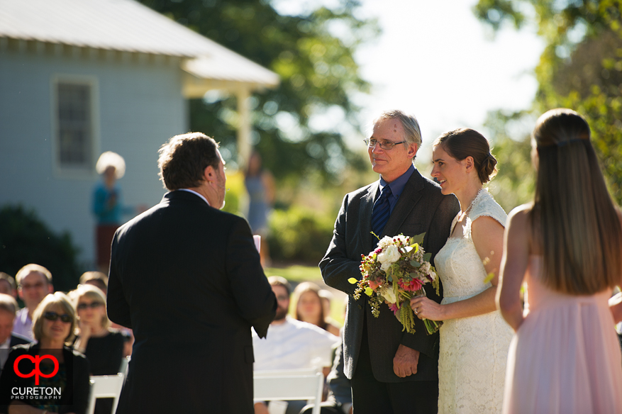 Father giving away his daughter at hear wedding.