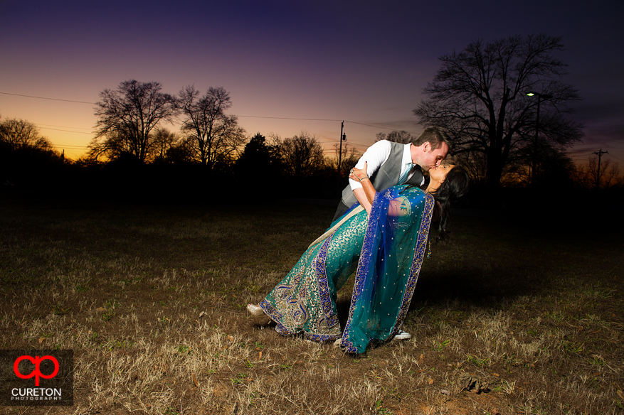 Groom dipping the bride at sunset outside the Loom in Simpsonville after their wedding.