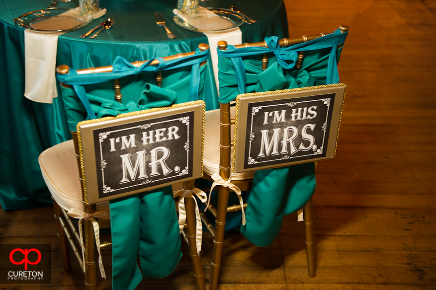 Mr. and Mrs. sign for wedding reception seats.