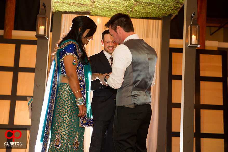 Groom putting a ring on the brides finger.