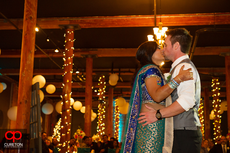 Married couple kissing after their first dance.