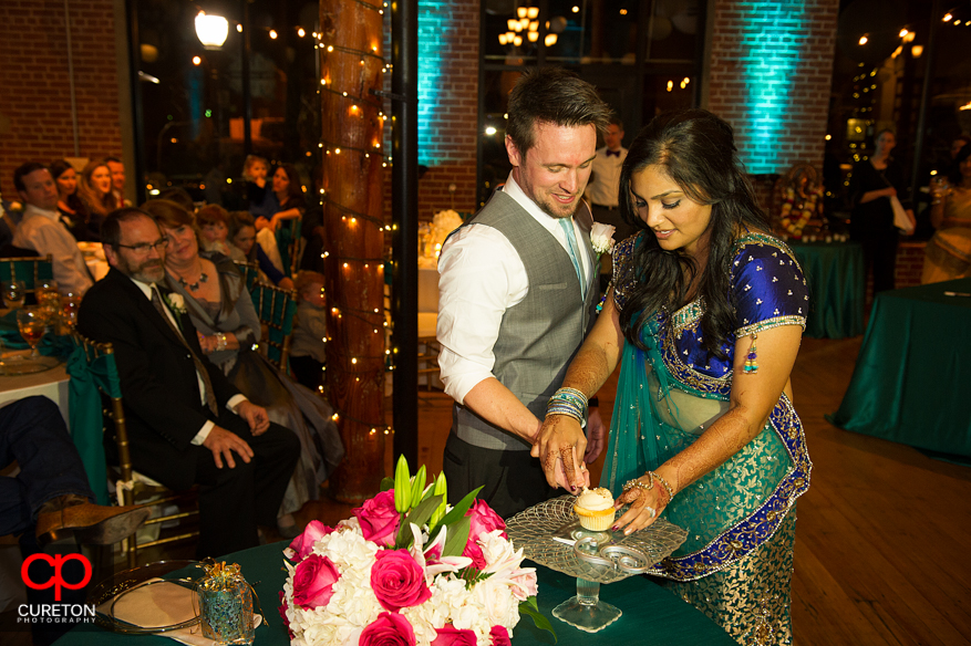 Bride and Groom cutting the cake at their Indian wedding reception.