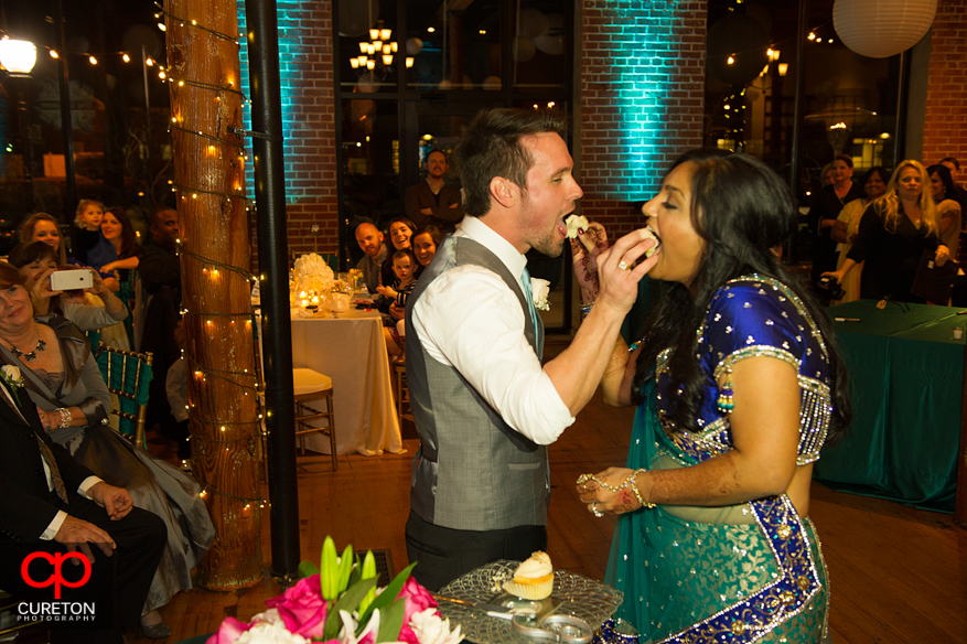 Bride and Groom feeding each other cake at their Indian wedding reception at The Loom.