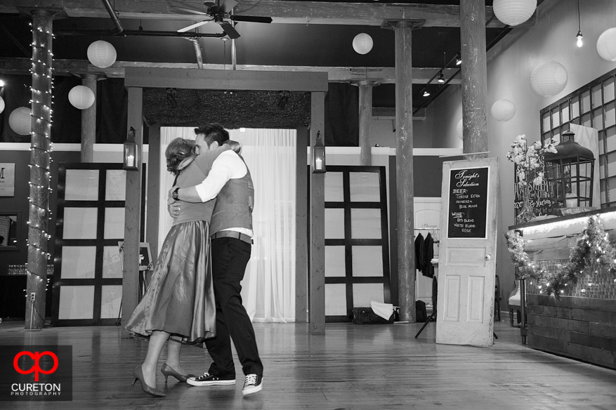 Groom and mom hugging after their dance.